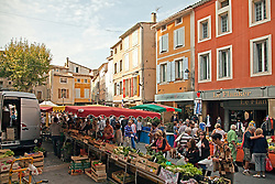 Vintage clothing, toys, and antiques share sidewalk space with amazing food and working artists during the Sunday flea markets for which the town of L'Isle-sur-la-Sorgue is famous.