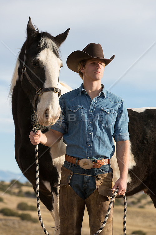 handsome cowboy walking on a ranch with a painted horse