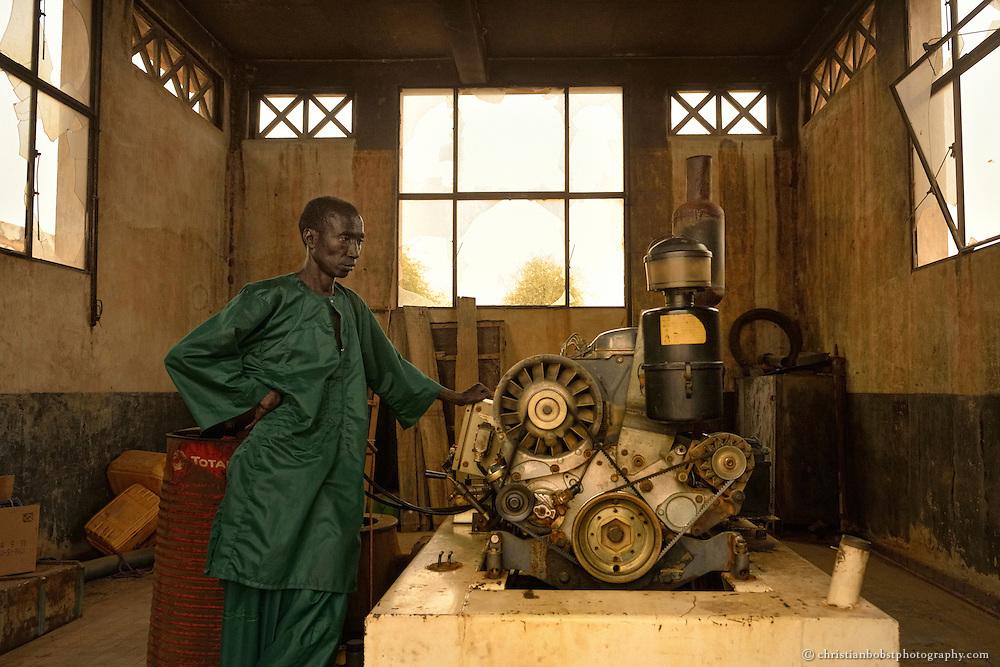 """Dank einem von HEKS mitfinanzierten Bohrbrunnen können Viehbauern im sehr heissen und trockenen YOUNOUFERE in Senegal ihre Kühe auch in der Trockenzeit mit frischem Wasser versorgen. Auf dem Bild sieht man den Motor und den """"Conducteur""""  des Bohrbrunnens."""