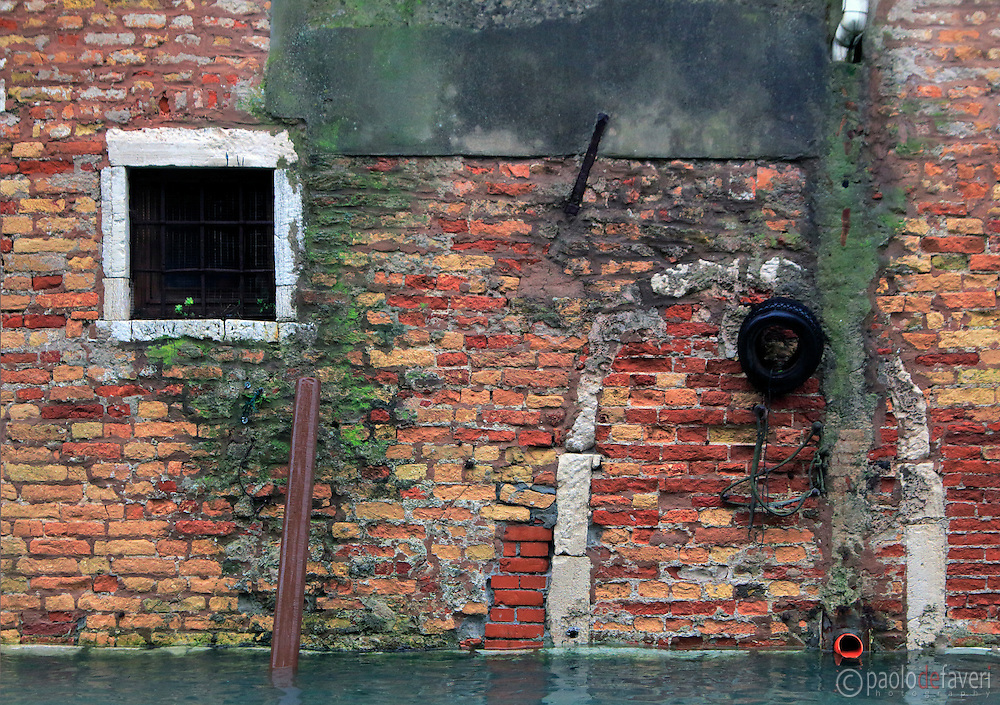 The wall of a small house on Rio della Sensa, a canal in the Sestiere of Cannaregio in Venice, Italy
