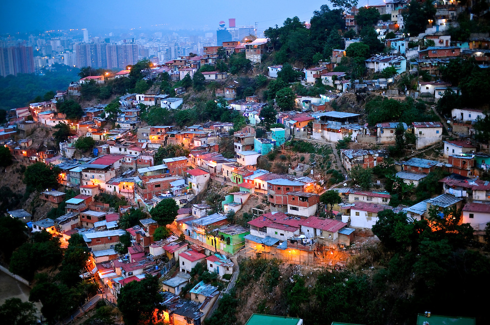 Hillside slums at dusk in Caracas, Venezuela. The Venezuelan government commissions young graffiti artists to plaster the slums in murals and stencils that promote the Bolivarian revolution and the political agenda of President Hugo Chavez.
