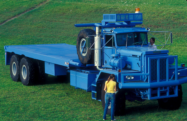 Large blue flatbed transportation truck parked in a field of grass as a woman makes inspections
