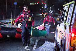 © Licensed to London News Pictures . 26/12/2015 . Salford , UK . Mountain rescue team carrying a canoe along Lower Broughton Road as residents were evacuated from surrounding streets following flooding . Photo credit : Joel Goodman/LNP