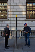 Two London tourists read a city map information post in Whitehall, Westminster.