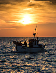 © Licensed to London News Pictures. 16/10/2018. Hastings, UK. RX445 steams into shore. Daybreak over the English Channel, fisherman bring in the morning catch under unseasonably warm conditions. Hastings has one of the last functioning and the largest beach-launched fishing fleet in Europe. Boats intentionally run aground on reinforced keels and are winched up out the water by bulldozer. Photo credit Guilhem Baker/LNP