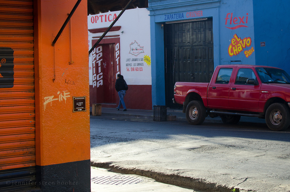The morning sun lights up vivid colors on a street corner in Oaxaca, Mexico.