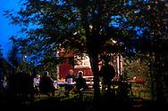 Men drinking under a tree late at night during a village party in Västanvik, Sweden