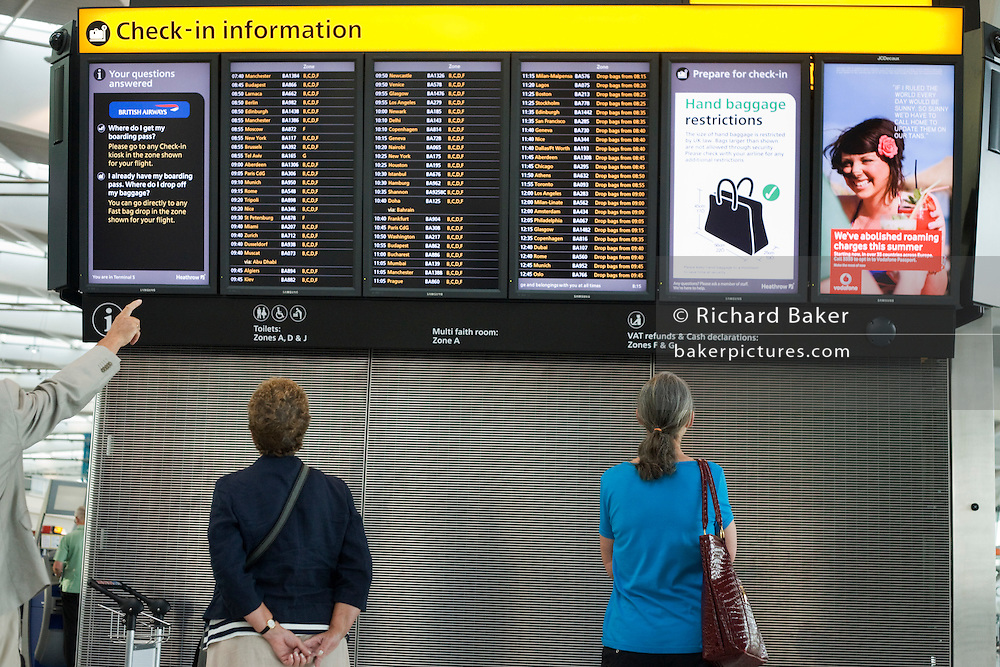 "A departures information board at Heathrow Airport's Terminal 5 is viewed by passengers who stands motionless to read the details of flight departure times to echo that of a Vodafone advertisement containing a tourist on a beach, a generic scene of a person on holiday taking advantage of low mobile phone charges in mainland Europe.  A finger from an unseen traveller points to a flight time and to ladies stand gazing up at the check-in guide that helps tell which is the check-in zone of this 400 metre-long terminal that has the capacity to serve around 30 million passengers a year. From writer Alain de Botton's book project ""A Week at the Airport: A Heathrow Diary"" (2009). .."