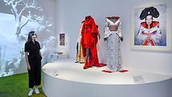 "© Licensed to London News Pictures. 26/02/2020. LONDON, UK. A staff member views works on display, including a kimono worn by singer Bjork (R). Preview of ""Kimono: Kyoto to Catwalk"", an exhibition celebrating the Japanese kimono.  Artworks are on show at yje V&A museum in South Kensington 29 February to 21 June 2020.  photo credit: Stephen Chung/LNP"