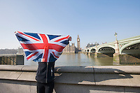 Woman holding British flag in front of face against Big Ben at London; England; UK