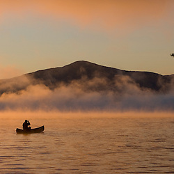 Canoeing in Lily Bay at sunrise, Moosehead Lake, Maine.  Lily Bay Mountian is in the distance.