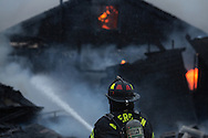 (Gabe Green   The Daily World)<br /> <br /> An Aberdeen fire fighter douses the collapsed roof of a home which was set fire to by the owner Wednesday morning on the 1500 block of Aberdeen Avenue.