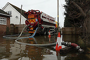 Flood water is pumped into tankers to be removed from Ham Island on the river Thames near Old Windsor. Thames Valley. UK