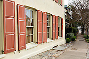 A colorful pastel building facade and painted shutters along East Bay Street in historic Charleston, SC.