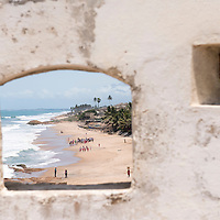 View of locals on the beach through a window in a fortified wall of the Cape Coast Castle, a UNESCO World Heritage Site located along the Gold Coast of Ghana.