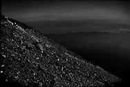 On the 27th of September 2014 out of the blue, on a perfect day, like this one on Mt Fuji, Ontake Volcano lured over 300 hikers to the climb when hot volcanic gas and cinders were sent skyward and then rained down on largely helpless climbers killing 57 and 6 are still missing as winter snow ended recovery missions until spring.  If this were to happen on Mt. Fuji, the death toll could be much higher.  Retired Ryukyu University professor Masaki Kimura believes Mt. Fuji should have erupted in 2011 (with a four-year margin of error) because the pressure in the magma chamber is believed to be higher than it was when it last erupted over 400 years ago.  More worrisome, Professor Kimura says that magma is rising and cracks in the earth have been growing.  <br /> <br /> The final Shinto torii gate (top left) just below the summit can be seen on Mt. Fuji, which is actually a huge Shinto holy site.   A continuous line of climbers ascend Mt. Fuji just after dawn.  Mt. Fuji has long attracted masses of climbers to the point that there are human traffic jams on the trail leading up the mountain, when there can be up to 10,000 hikers on the mountain during the summer climbing season from early July to early September.