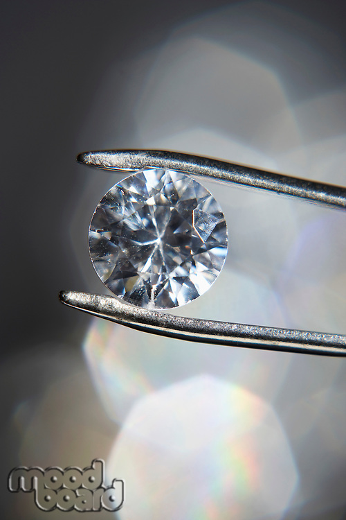 Diamond held by tweezers close-up