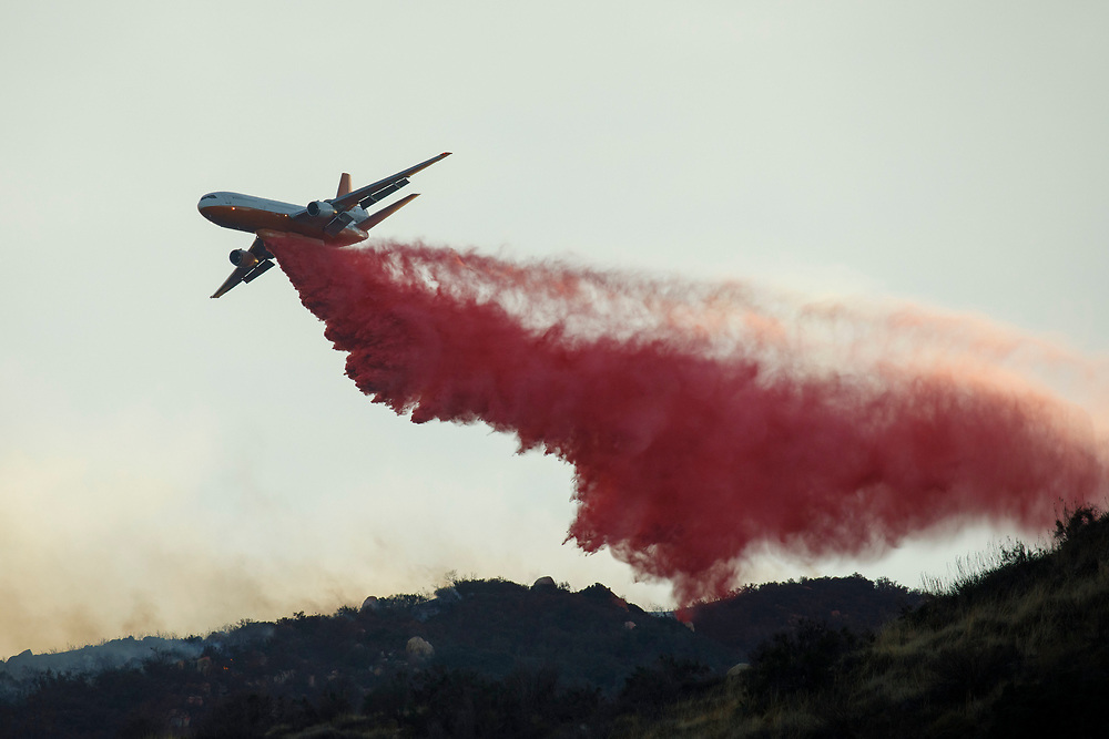 A resident takes a video as the Cal Fire DC-10 firefighting aircraft battles the Wildomar wildfire in the Cleveland National Forest on Thursday, October 26, 2017 in Wildomar, Calif. The fire started after a motorcycle crashed into a tree. © 2017 Patrick T Fallon