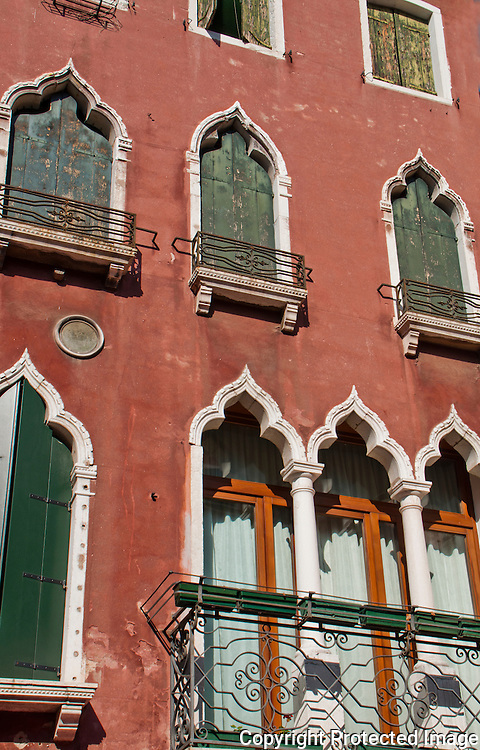 Exotic red building facade with green wooden shutters and oriental style arched windows in Venice, Italy.