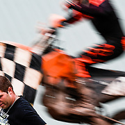 A checkered flag is waved as a motorbike crosses the finish line at a motocross competition.