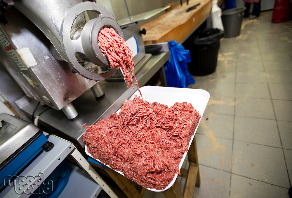 Minced meat falling from machine in container at store