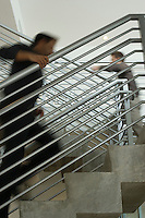Two office workers walking up stairs