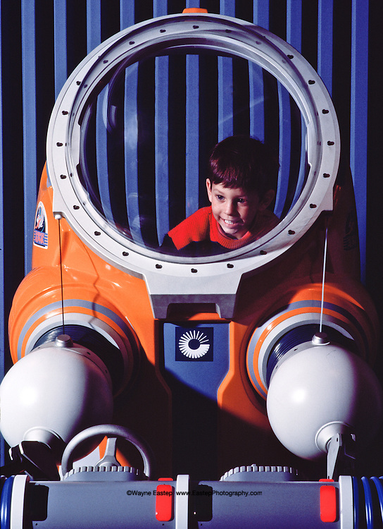 A young visitor at The Living Seas tries his hand at operating JIM suit controls. EPCOT, Buena Vista, Florida