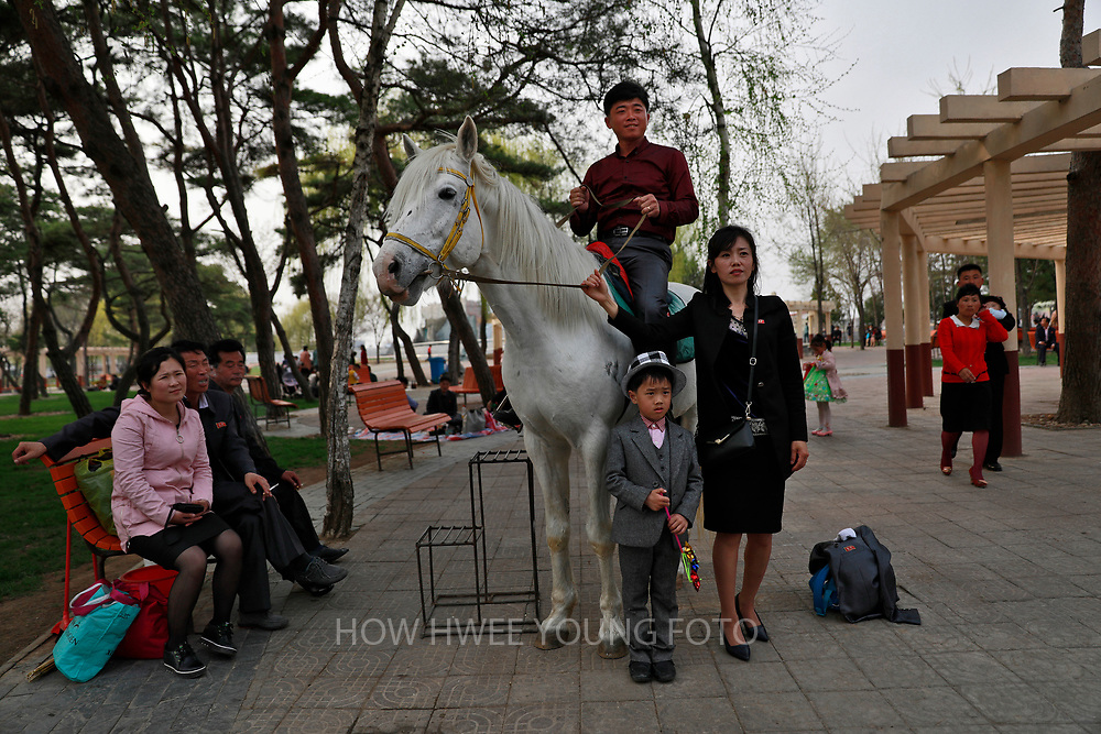 A picture made available on 17 April 2017 of a North Korean family posing for photos with a horse at the Central Zoo in Pyongyang, North Korea, 16 April 2017. A North Korean missile exploded within seconds of its launch on the east coast on 16 April, South Korean and US officials say as tensions rise in the region over nuclear issues.