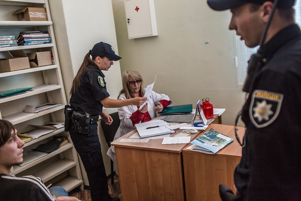 LVIV, UKRAINE - SEPTEMBER 16, 2015: Members of the new Lviv police, including Tetiana Soroka, 25, second from left, fill out paperwork connected to a routine medical exam for Vladimir, 26, left, after arresting him when he was found intoxicated and sleeping in the city's central square and then swore at police officers in Lviv, Ukraine. In an effort to reform the notoriously corrupt Ukrainian police force, an entirely new force has been established in several cities, including Kiev and Lviv, with a primary focus on patrolling the streets. CREDIT: Brendan Hoffman for The New York Times
