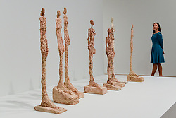 "© Licensed to London News Pictures. 08/05/2017. London, UK. A staff member views plaster works in the series ""Woman of Venice"", 1956.  Preview of the UK's first major retrospective of Alberto Giacometti for 20 years at Tate Modern.  The exhibition runs 10 May to 10 September 2017. Photo credit : Stephen Chung/LNP"