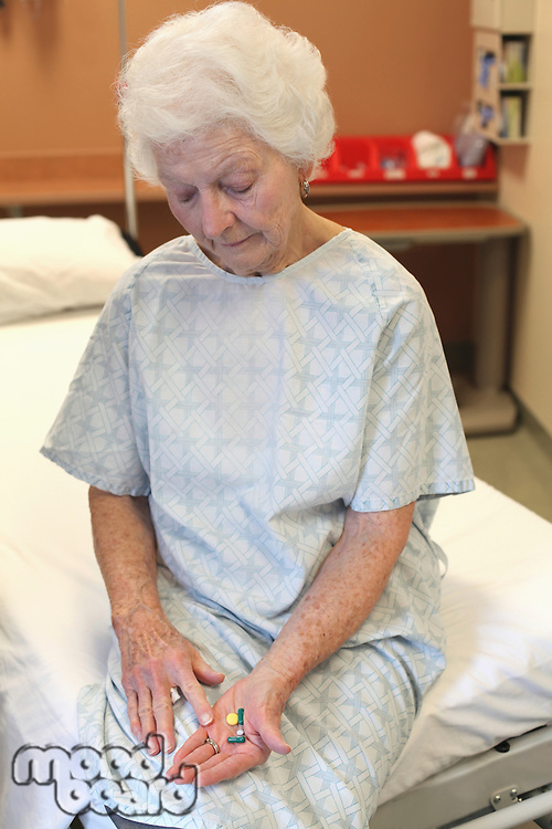 An old lady in a hospital gown  sitting on a bed  looking down at several pills in her hand