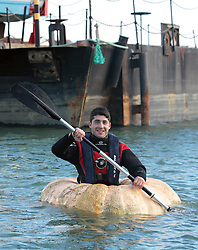 Pumpkin Boat. <br /> Artist Dmitri Galitzine after setting a new Guiness World record for the fastest hundred metres paddled in a Pumpkin boat at Trafalgar Wharf, Port Solent, Portsmouth, United Kingdom. Wednesday, 23rd October 2013. Picture by Matt Scott-Joynt / i-Images.<br /> UK OUT