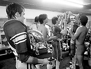 Fox, OK, football players are more interested in the bottle of champagne making the rounds than they are in the championship trophy in the locker room after winning the Class A State Championship against Dewar, OK.