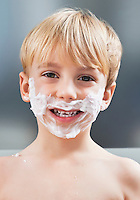 Portrait of Caucasian boy with shaving cream on his face