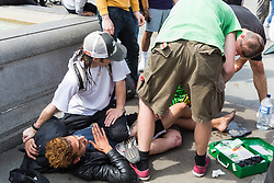 """Street performers restrain an alleged pickpocket while first aid is administered to the man who chased him down and caught him. Street performers demanded that Romanian pickpockets desist from """"working"""" on the North Terrace of Trafalgar Square where they steal from crowds watching the street entertainers. London, August 02 2019."""