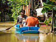 30 SEPTEMBER 2016 - SAI NOI, AYUTTHAYA, THAILAND:  People paddle back to their home in Sai Noi, a village flooded by the Chao Phraya River. The Chao Phraya River, the largest river that runs through central Thailand, has hit flood stage in several areas in Ayutthaya and Ang Thong provinces. Villages along the river are flooded and farms are losing their crops due to the flood. This is the same area that was devastated by floods in 2011, but the floods this year are not expected to be as severe. The floods are being fed by water released from upstream dams. The water is being released to make room for heavy rains expected in October.     PHOTO BY JACK KURTZ