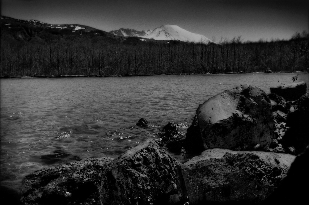 These large, volcanic boulders in the foreground were once part of Mt. St. Helens which rises above the ridge 17 km (10.56 miles) away.  This lake did not exist before Mt. St. Helens erupted in 1980.  It was created by a dam of lahar mud that blocked a stream.  The forest on the far bank is part of nature's post-eruption recovery.