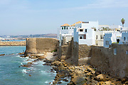 Portuguese Rampart Architecture, Asilah, Northern Morocco, 2015-08-11.<br /><br />Asilah is a sleepy fishing town in the North of Morocco, just one hour south of Tangier. While not completely off Morocco's well-beaten path, it's often missed by travellers bound inland for Fez or Chefchaouen, yet has a uniquely alluring charm. With an immaculately restored medina that's re-painted vivid shades of blue & white each summer, Asilah has the feel of being Morocco's own Santorini - a great spot to see the more chilled out, seaside town life in Morocco.  <br /><br />The town lies in the middle of a fascinating history in historical, architectural and artistic terms. It's 3,600 year old history that includes a varied range of occupiers, involving Roman, Arab Portuguese, Spanish and French colonisation. Many famous writers and artists have spent time here; in ancient times is it reported Herecules did a tour of the area and, more recently; Paul Bowles, Tennessee Williams, Edith Wharton, Jean Genet (who is buried in the nearby town of Larache), William Burroughs, Jimi Hendrix and Henri Matisse have all found the area inspiring. The Portuguese ramparts remain fully intact and a full day can be spent wandering through its old gates and the ever narrowing medina streets inside the walls.<br /><br />The architecture in Asilah has been heavily influenced by these different periods of occupation, which is one of the main reasons for its unique and characterful feel. Evidence of Mediterranean design can be seen in the rampart walls and gates themselves, reflecting the Spanish & Portuguese influence on the Asilah's development, Roman ruins can be found in the nearby town of Larache and Arab influences are more subtly found in the decorative window shutters and the labyrinth like medina layout to the streets. <br /><br />If a lover of the quirkier details found in the medinas of Morocco, then Asilah won't disappoint, with hundreds of creatively designed doorways, decorative window shut