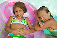 Two girls (7-9) in swimming pool portrait.