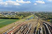 Nederland, Zuid-Holland, Zwijndrecht, 23-10-2013; Kijfhoek, rangeerterrein voor goederentreinen. Overzicht van de verdeelsporen (richting Zwijndrecht). Kijfhoek huisvest Keyrail, exploitant Betuweroute en is in beheer bij ProRail. De Betuweroute, die begint als Havenspoorlijn op de Maasvlakte, verbindt via Kijfhoek de Rotterdamse haven met het achterland. Het rangeeremplacement dient voor het sorteren van goederenwagons waarbij gebruik gemaakt wordt van de zwaartekracht, het 'heuvelen': de wagons worden de heuvel opgeduwd, bij het de heuvel afrollen komen ze, door middel van wissels, op verschillende verdeelsporen. Railremmen zorgen voor het automatisch remmen van de wagons. Na het heuvelproces staan de nieuw samengestelde treinen op aparte opstelsporen.<br /> Kijfhoek, railway yard used by ProRail and Keyrail (Betuweroute operator). Kijfhoek connects via the Betuweroute (beginning as Havenspoorlijn on the Maasvlakte), through the port of Rotterdam with the hinterland. The shunting yard for sorting wagons makes use of gravity. The new trains are assembled on separate tracks.<br /> luchtfoto (toeslag op standard tarieven);<br /> aerial photo (additional fee required);<br /> copyright foto/photo Siebe Swart