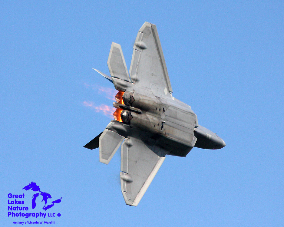 In this image from EAA Airventure 2008, the pilot of this F-22 Raptor performs a maximum thrust turn away from the audience lining the runway at Whitman Airport in Oshkosh, Wisconsin. The afterburner flames give some hint of the sound volume (my ears were still ringing two days later).
