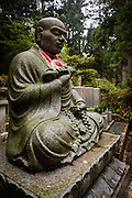 The statue of a Buddhist monk praying and counting his beads.
