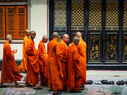 """05 SEPTEMBER 2017 - BANGKOK, THAILAND: Mahayana Buddhist monks walk into a prayer service for Hungry Ghost Day at Wat Mangon Kamalawat in Bangkok's Chinatown. The Ghost Festival is a Buddhist and Taoist holy day celebrated on the 15th day of the 7th lunar month. It is primarily celebrated in China and Chinese communities outisde China. In Thailand, it's celebrated in Thai-Chinese communities in Bangkok, Phuket and Chiang Mai.  On that day ghosts and spirits, including those of the deceased ancestors, come out from the lower realm to visit the living. Families prepare elaborate banquets for the spirits and burn """"ghost money"""" for the spirits to use in the other realm. It is a day for venerating dead relatives.      PHOTO BY JACK KURTZ"""