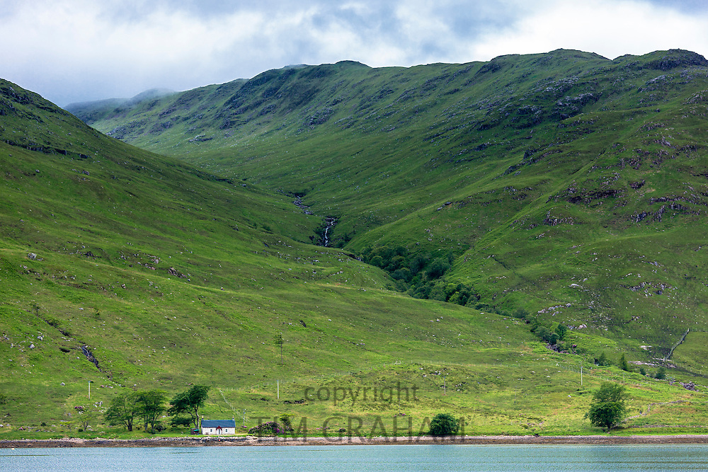 Traditional Scottish small white croft cottage on the shores of Loch a Choire in the shadow of Beinn Mheadhoin mountain in Western Highlands of Scotland