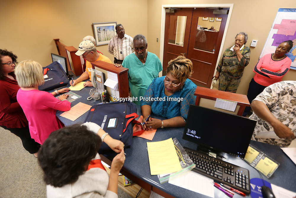 Poll workers for the different precincts in Tupelo, gather inisde the city clerk's office to receive their election equipment to prepare for Tuesday's primary election.