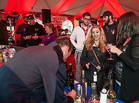 Eliza Rae-Beck and Ashley Beck try a Chop Shop Cabernet from Mac Bird with Crush Wines during the Red, White and Brew Fest at Funspot on Saturday afternoon.  (Karen Bobotas/for the Laconia Daily Sun)