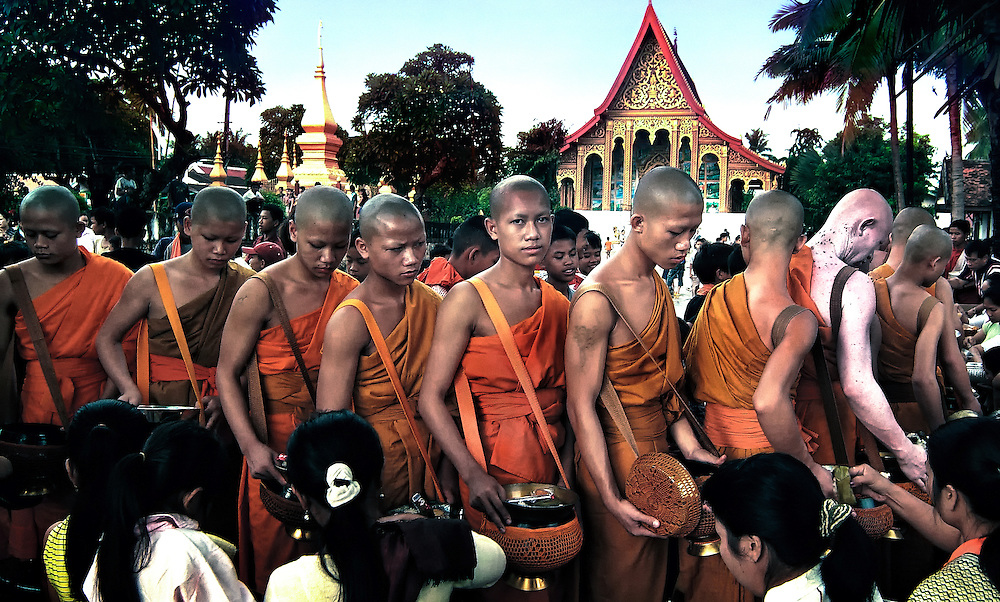 Novices and monks collect alms at Wat Manorom, Luang Prabang, Laos.