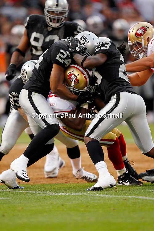 San Francisco 49ers running back Brian Westbrook (20) gets gang tackled by Oakland Raiders safety Michael Huff (24) and Raiders cornerback Jeremy Ware (23) during the NFL preseason week 3 football game against the Oakland Raiders on Saturday, August 28, 2010 in Oakland, California. The 49ers won the game 28-24. (©Paul Anthony Spinelli)