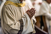 Priest with hands folded in prayer during Catholic mass.