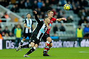 James Ward-Prowse (#16) of Southampton and Miguel Almiron (#24) of Newcastle United battle for the ball in the air during the Premier League match between Newcastle United and Southampton at St. James's Park, Newcastle, England on 8 December 2019.